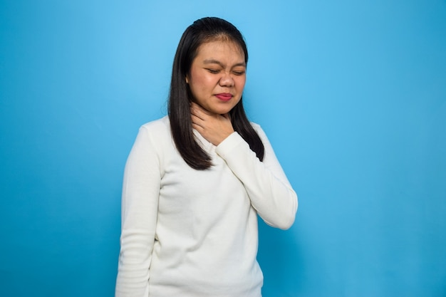 Donne asiatiche che usano una maglietta bianca con sfondo blu isolato donne mal di gola covid19