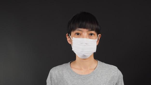 Le donne asiatiche indossano la maschera facciale su sfondo nero.