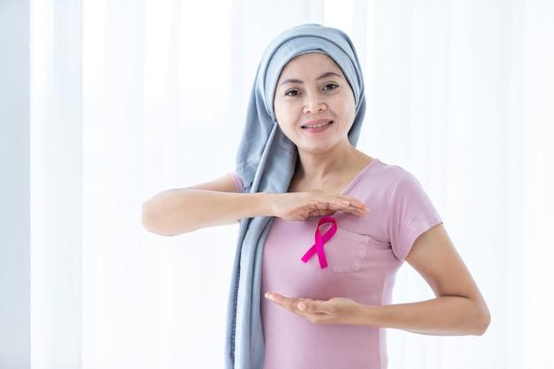 Una donna asiatica che indossa la malattia del velo con la mano del nastro rosa che controlla i grumi sul seno per segni di cancro al seno isolato alla finestra nella camera da letto a casa, assistenza sanitaria, medicina