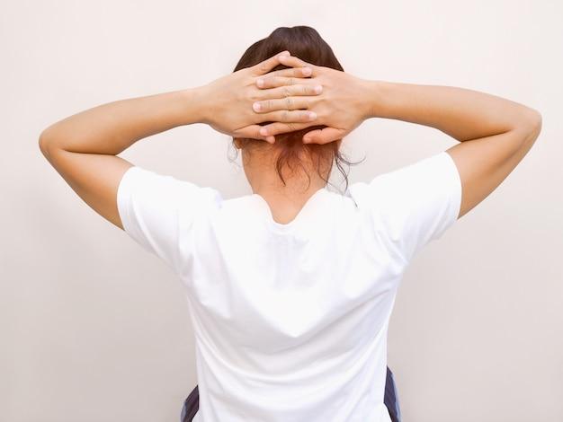 Donne asiatiche con posture di esercizio con il sollevamento della mano e l'allungamento dei muscoli e il contatto occipitale per alleviare dolori alla schiena e mal di testa.