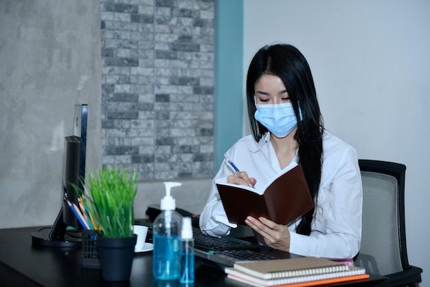 Le donne asiatiche lavorano a casa. per confinarsi durante il virus corona indossando una maschera e lavandosi le mani disinfettando per prevenire covid-19