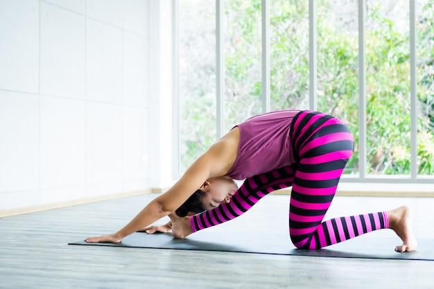 L'allenamento asiatico delle donne che pratica l'addestramento di yoga ha messo i vestiti rosa e pratica la meditazione