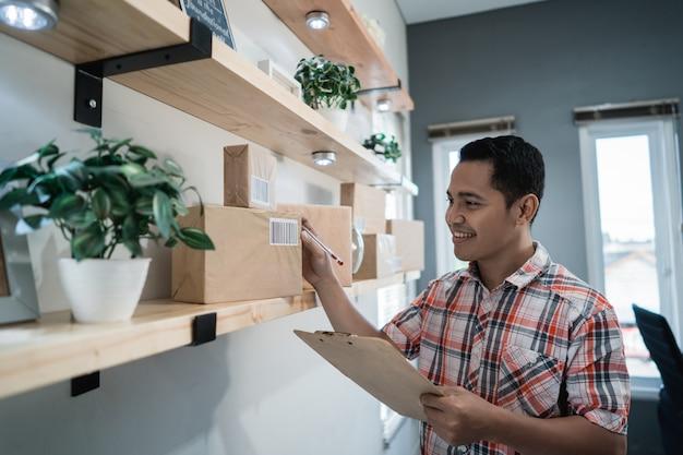 Sguardo asiatico del lavoratore alle scatole su uno scaffale di legno nella stanza e nel controllo dell'ufficio