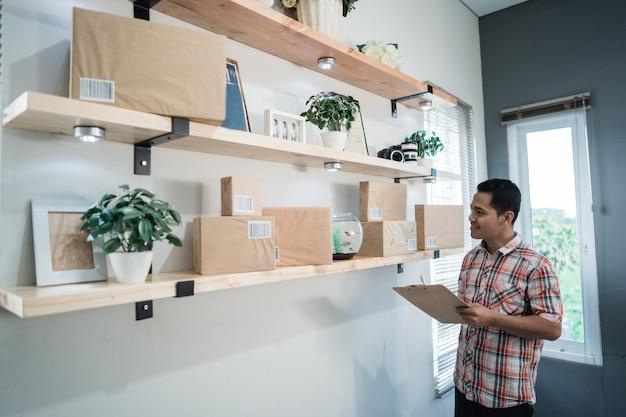 Sguardo asiatico del lavoratore alle scatole su uno scaffale di legno nella stanza dell'ufficio