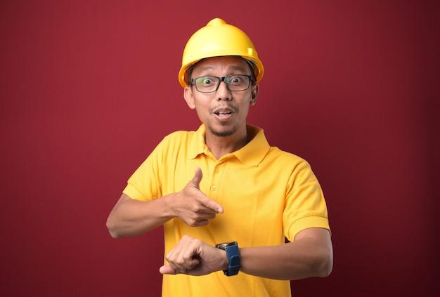 Un lavoratore asiatico che indossa il casco in fretta indicando di guardare il tempo sconvolto e arrabbiato per il ritardo della scadenza
