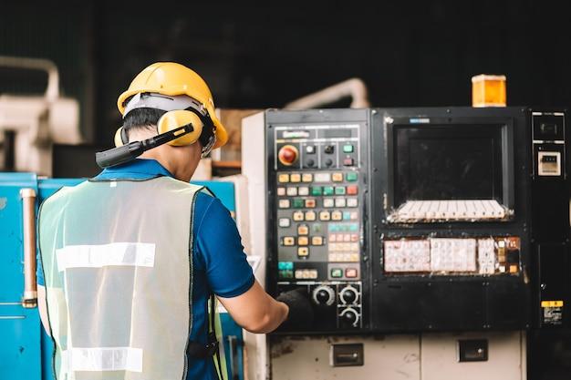 Uomo dell'operaio asiatico che lavora in abbigliamento da lavoro di sicurezza con casco giallo utilizzando computer portatile digitale.