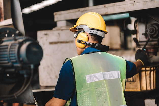 Uomo asiatico dell'operaio che lavora in abbigliamento da lavoro di sicurezza con il casco giallo.