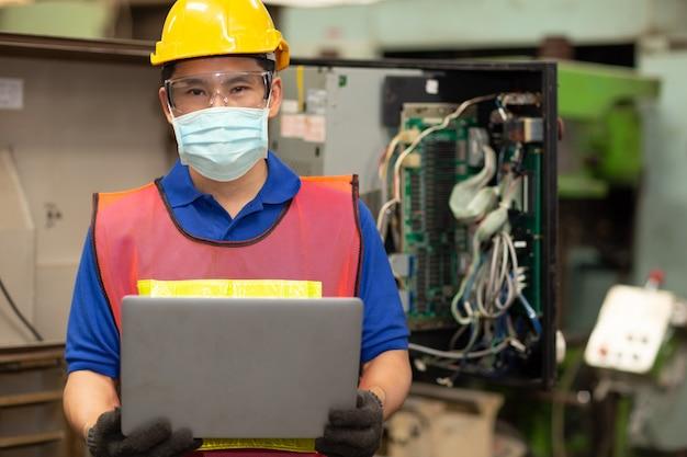 Il lavoratore asiatico indossa una maschera facciale usa e getta per la protezione diffusione del virus corona e filtro per l'inquinamento dell'aria da polvere di fumo in fabbrica per una sana assistenza al lavoro.