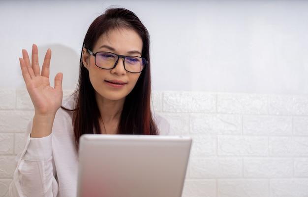 Asian che lavora a casa utilizzando un dispositivo tablet, videochiamata con un amico.