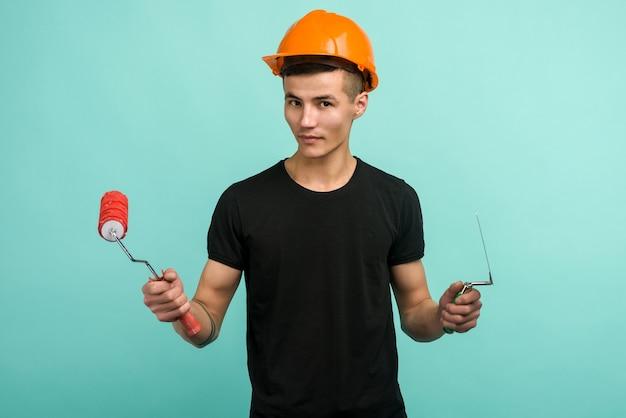 L'uomo di lavoro asiatico in un casco arancione sta con un rullo di vernice