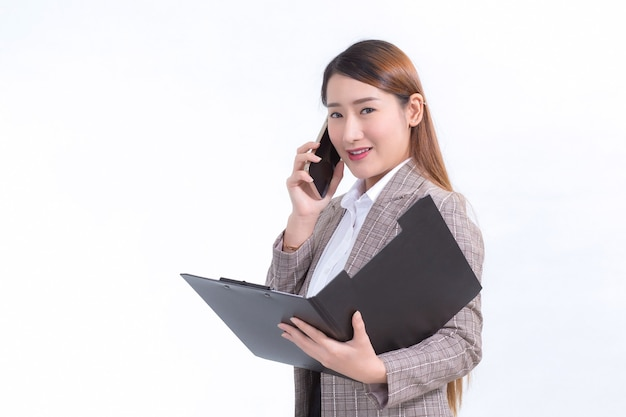 La donna lavoratrice asiatica in abito formale con camicia bianca sta chiamando il telefono e apre file di documenti o appunti per controllare i dati.