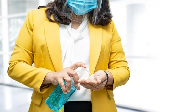 Donna lavoratrice asiatica lavarsi le mani premendo gel igienizzante alcol blu