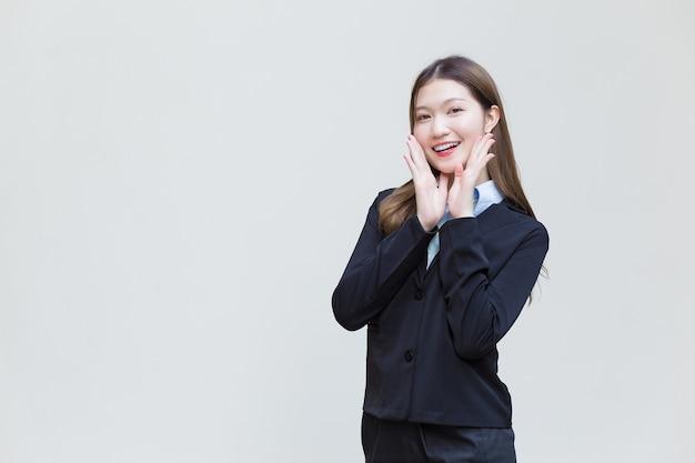 La donna lavoratrice asiatica che ha i capelli lunghi indossa un abito formale nero con una camicia blu mentre sorride felicemente su sfondo bianco.