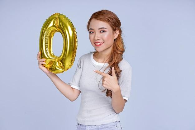 Giovane bella ragazza asiatica attraente giovane che tiene il numero di palloncino in lamina metallica