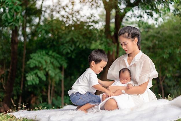Giovane bella madre asiatica ed i suoi bambini, neonata appena nata e un ragazzo che si siedono sull'erba verde per giocare e abbracciare nel parco