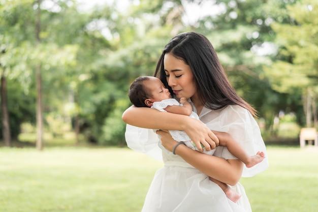 La giovane bella madre asiatica che tiene in braccio il suo neonato sta dormendo e si sente con amore e si tocca delicatamente poi si siede sull'erba verde nel parco