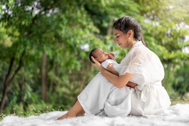 La giovane bella madre asiatica che tiene il suo neonato sta dormendo e sente con amore e toccando delicatamente quindi sedendosi sull'erba verde nel parco