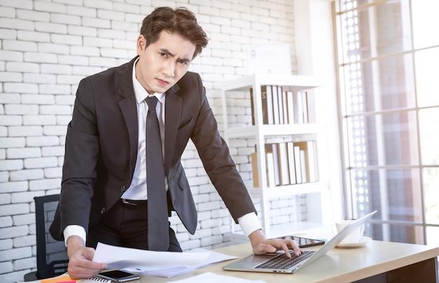 Il giovane uomo d'affari asiatico ha sottolineato vedere un piano aziendale del documento e un computer portatile su un tavolo di legno dopo perdite aziendali sullo sfondo della stanza dell'ufficio.