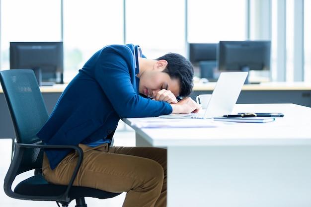Il giovane uomo d'affari asiatico ha lavorato tardi e si è addormentato sul computer portatile nella stanza dell'ufficio