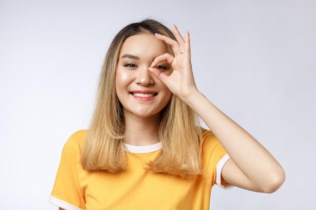 Giovane donna di affari asiatica con il gesto giusto del segno