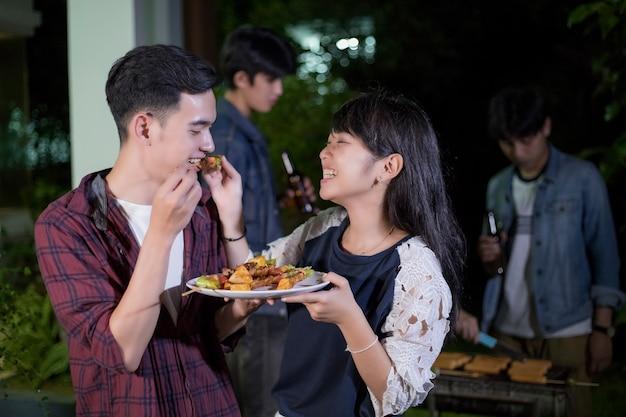 Giovani coppie asiatiche che godono di una cena romantica e un gruppo di amici che hanno barbecue esterno del giardino l