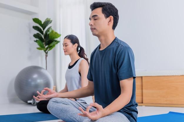 Le giovani coppie asiatiche esercitano e giocano insieme yoga a casa