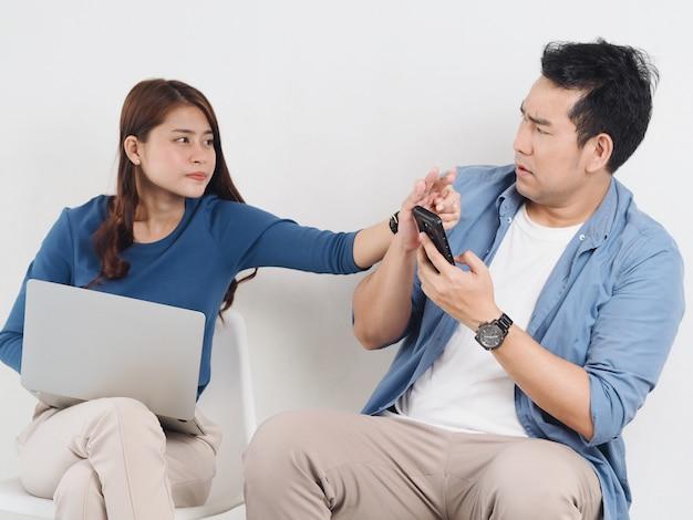 Giovane amante asiatico delle coppie che combatte per uno smart phone in salone a casa.