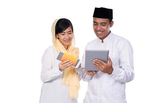 Giovani coppie asiatiche musulmane che per mezzo del pc della compressa