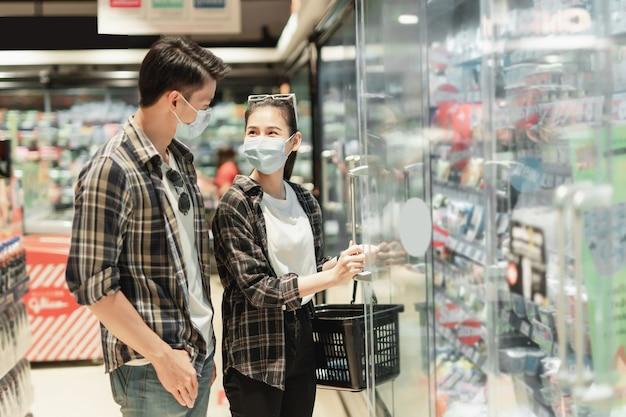 Giovani coppie asiatiche in maschera di protezione da scegliere per lo shopping di cibi surgelati durante l'epidemia di coronavirus
