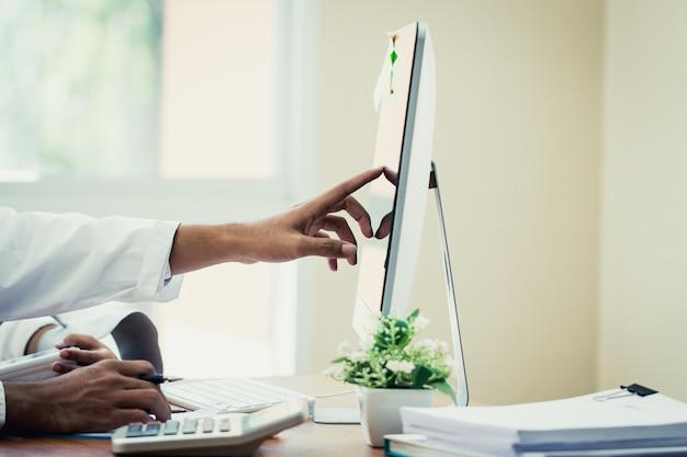 Giovane medico asiatico che legge il controllo per informazioni nel computer, spiega i risultati di buone notizie del trattamento
