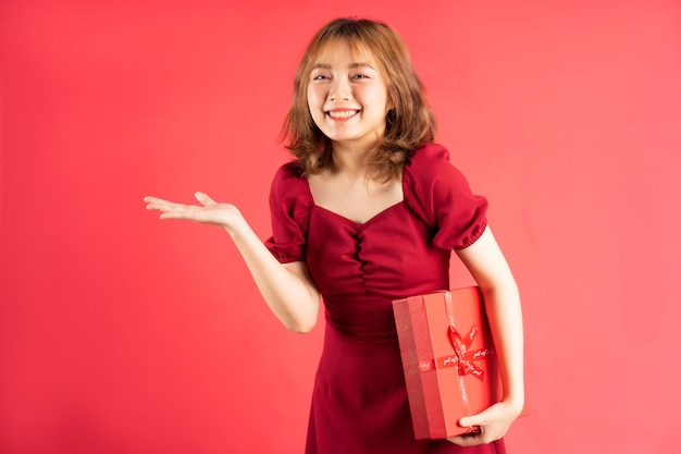 Ragazza asiatica in abito con scatola regalo rossa con espressione allegra sul rosa