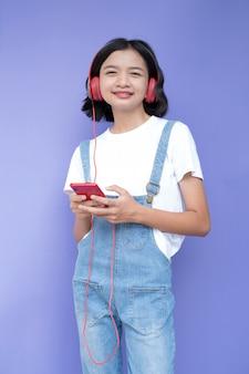 La ragazza asiatica ascolta musica con lo smartphone rosso sulla porpora