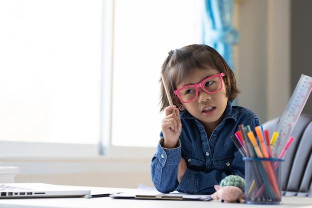 La ragazza asiatica studia il soggiorno online a casa.