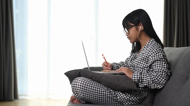 Ragazza asiatica che utilizza computer portatile studiando i compiti durante la sua lezione online a casa.