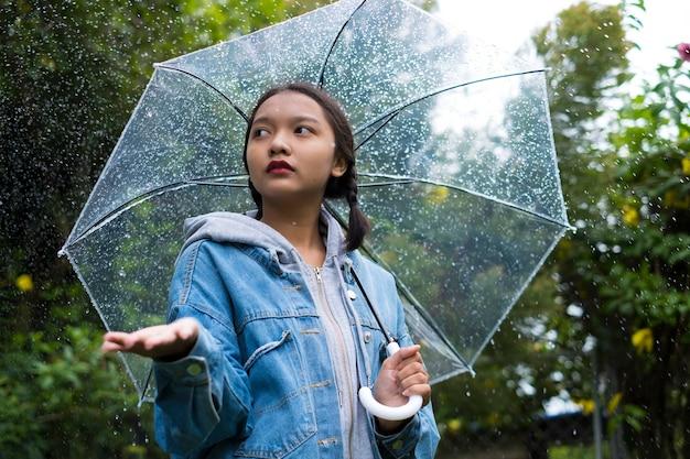 La ragazza asiatica indossa la giacca di jeans con l'ombrello in giardino.
