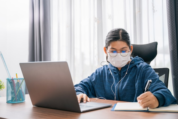 Ragazza asiatica indossa una maschera studente con occhiali cuffie ragazza studio felice scrittura nota su un libro guardando videoconferenza computer portatile online internet apprendimento formazione a distanza a casa