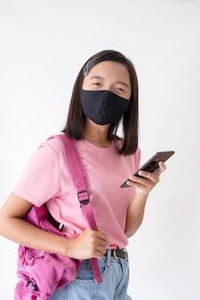 La ragazza asiatica indossa la maschera usando il cellulare su sfondo bianco