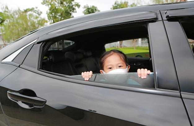 Una ragazza asiatica che indossa una maschera igienica sporge la testa fuori dal finestrino dell'auto durante l'epidemia di coronavirus (covid-19)