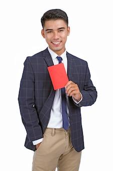 Il giovane uomo allegro bello asiatico di affari tiene il passaporto e il biglietto aereo