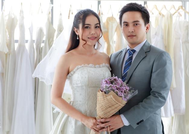 Asiatico giovane bello sposo in abito formale grigio con cravatta in piedi guarda la macchina fotografica con bella sposa felice in abito da sposa lungo bianco che tiene per mano e bouquet di fiori insieme nello spogliatoio.