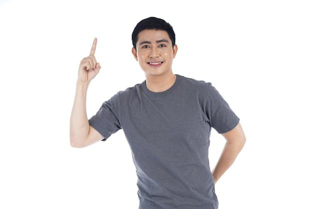 Giovane uomo bello asiatico nell'uso casuale che indica con il dito