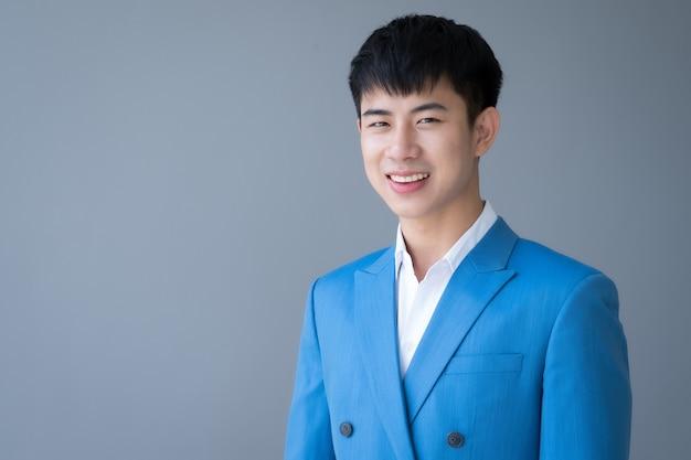 Giovane uomo bello asiatico che sorride in vestito