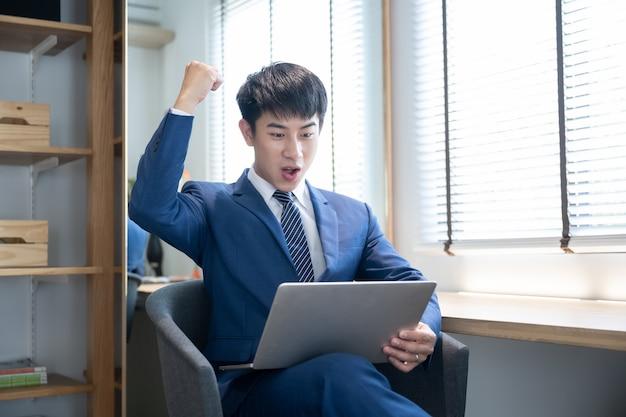 Giovane uomo bello asiatico che per mezzo del computer portatile