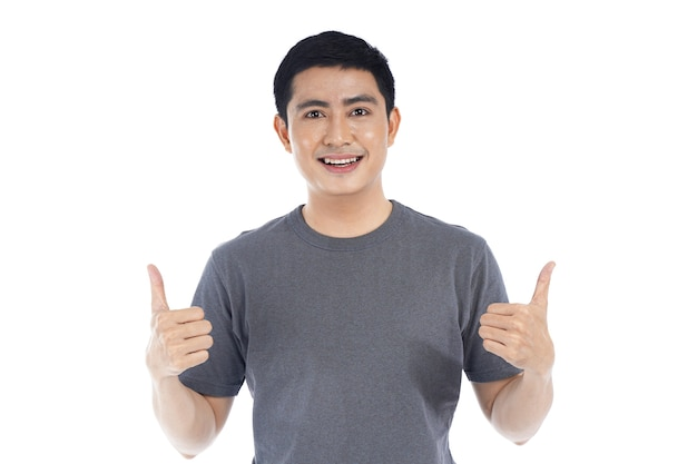 Giovane uomo bello asiatico con il pollice in su su bianco
