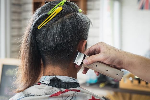 Giovane asiatico che viene tagliato da capelli lunghi a capelli corti con macchinetta elettrica da barbiere professionista nel negozio di barbiere.