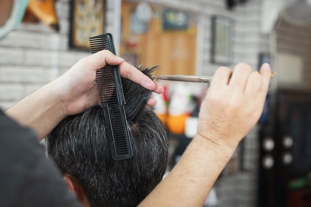 Giovane asiatico che è taglio di capelli con le forbici dal barbiere professionista nel negozio di barbiere. parrucchiere con pettine e forbici taglia i capelli.