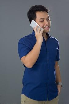Giovane asiatico in casuale facendo uso del telefono cellulare