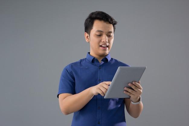 Giovane asiatico in casuale facendo uso della compressa