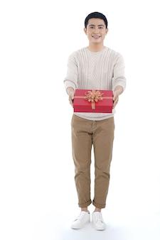 Giovane asiatico che dà il contenitore di regalo di natale con il nastro rosso