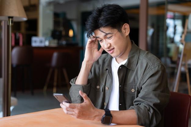 Smartphone asiatico della tenuta del giovane